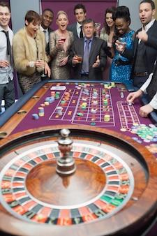 Ludzie stojący przy stole do ruletki