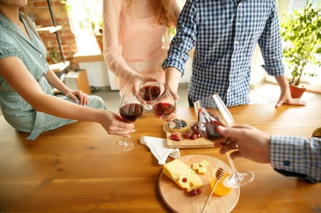 Ludzie stukają się kieliszkami z winem lub szampanem. wesołych wesołych przyjaciół