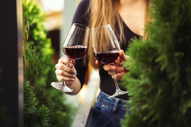Ludzie stukający się kieliszkami z winem na letnim tarasie kawiarni lub restauracji