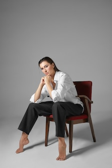 Ludzie, styl, moda, ubrania i koncepcja wnętrza. pionowy portret stylowej, pięknej, bosej młodej kobiety w męskim stroju, siedzącej na krześle jak mężczyzna z szeroko rozstawionymi nogami