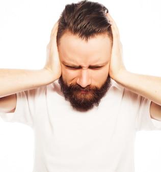 Ludzie, styl życia i koncepcja emocjonalna - brodaty mężczyzna zakrywający uszy rękami na białym tle