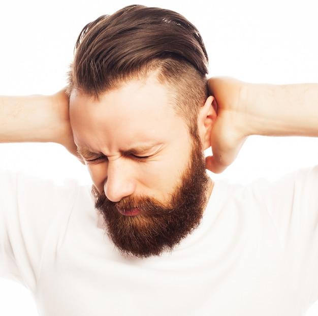 Ludzie, styl życia i koncepcja emocjonalna - brodaty mężczyzna zakrywający uszy rękami nad białą przestrzenią