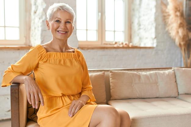 Ludzie, styl życia, wypoczynek, emerytura i relaks. kryty strzał pięknej modnej europejskiej emerytki w żółtej sukience siedzącej wygodnie na kanapie w salonie, uśmiechając się radośnie