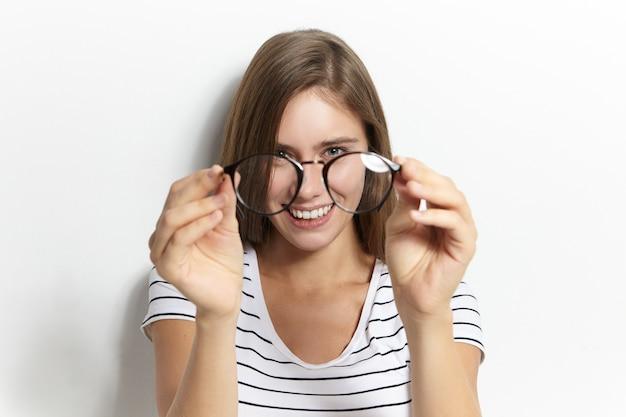 Ludzie, styl życia, zdrowie, okulary, optyka i koncepcja widzenia. portret szczęśliwa wesoła młoda kobieta trzyma stylowe okulary