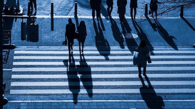 Ludzie sylwetka chodzić po przejściu dla pieszych z ciemnym cieniem ludzi
