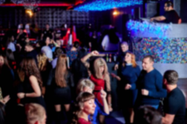 Ludzie tańczą na parkiecie w nocnym klubie, wiele osób. jasne światła stroboskopowe.