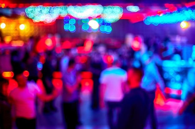 Ludzie tańczą, śpiewają, bawią się i odpoczywają w rozmytym tle nocnego klubu. błyski światła piękne rozmazane światła na parkiecie relaksują się w nocy w klubie