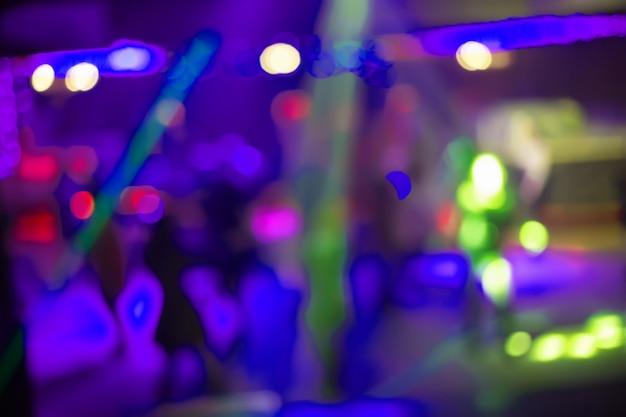 Ludzie tańczą, śpiewają, bawią się i relaksują w rozmazanej ścianie klubu nocnego.