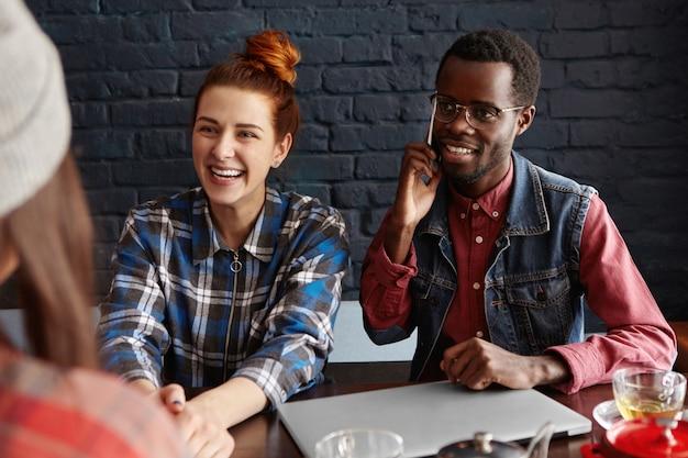 Ludzie, technologia i komunikacja. ładna dziewczyna z rudymi włosami rozmawia z koleżanką i śmiejąc się, stylowy afrykański mężczyzna w okularach siedzi przy stole obok niej
