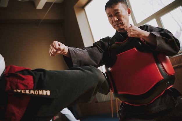 Ludzie trenują ze sprzętem ochronnym w pokoju sportowym.