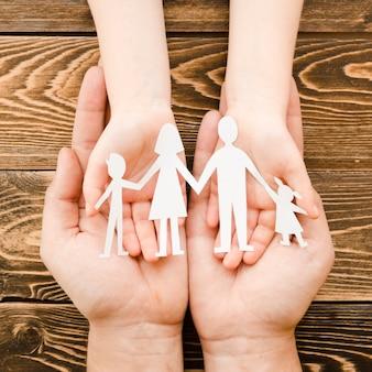 Ludzie trzyma papierową rodzinę na drewnianym tle