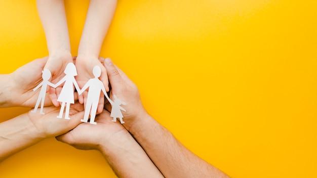 Ludzie trzyma papierową rodzinę w rękach na żółtym tle