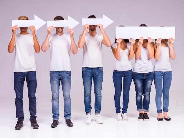 Ludzie trzymają strzały i zakrywają twarze.