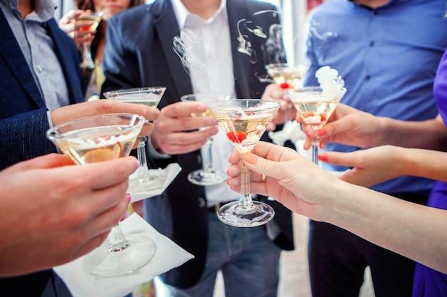 Ludzie trzymający kieliszki szampana, co toast, ręce w okularach