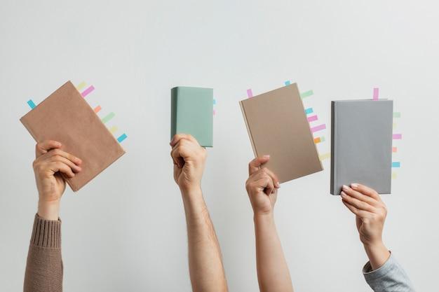 Ludzie trzymający książki z naklejkami przypominającymi kolorowe