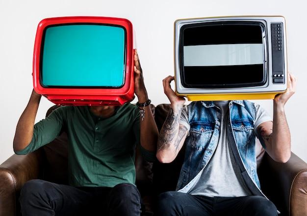 Ludzie trzymający retro telewizję obok siebie