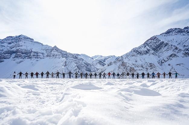 Ludzie trzymający się za ręce na znak pokoju z górami w tle zimą