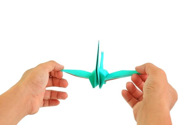 Ludzie trzymający się za ręce origami ptak na białym tle. koncepcja wolności