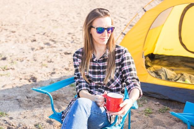 Ludzie, turystyka letnia i koncepcja przyrody - młoda kobieta siedzi w pobliżu namiotu
