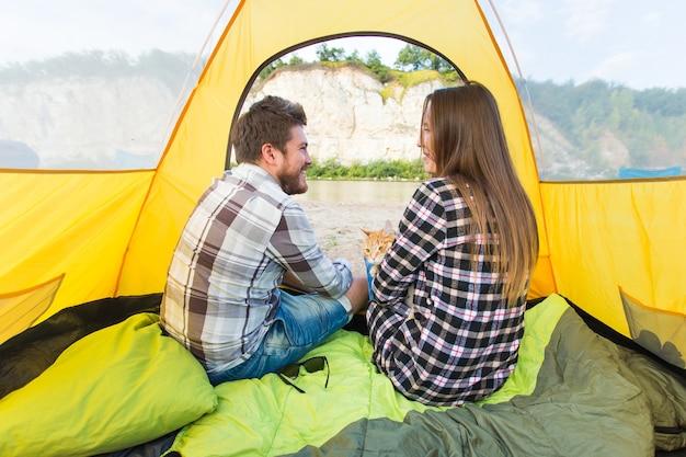 Ludzie, turystyka letnia i koncepcja przyrody - młoda para odpoczywa w namiocie kempingowym, widok od wewnątrz.