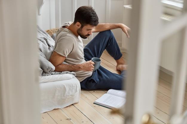 Ludzie, umiejętności, pojęcie wolnego czasu. skupiony, nieogolony mężczyzna w ciągu dnia pije świeży napój, skupiony na książce, czyta literaturę naukową, przygotowuje się do końcowego egzaminu, siedzi na podłodze. widok z drzwi