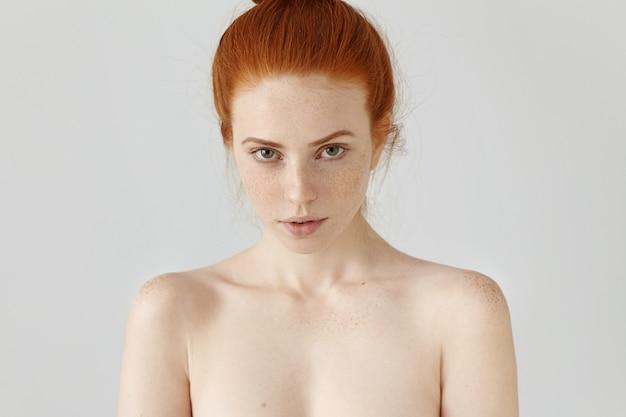 Ludzie, uroda i zdrowie. głowa i ramiona niezwykłej rudej modelki z piegami i świecącą skórą, pozująca nago na szarej ścianie
