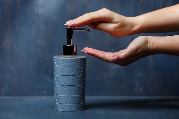 Ludzie używają dozownika mydła z metalową nasadką w kolorze szarym na szarym stole
