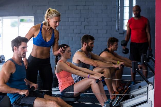 Ludzie używający maszyny do wiosłowania z instruktorem fitness w siłowni