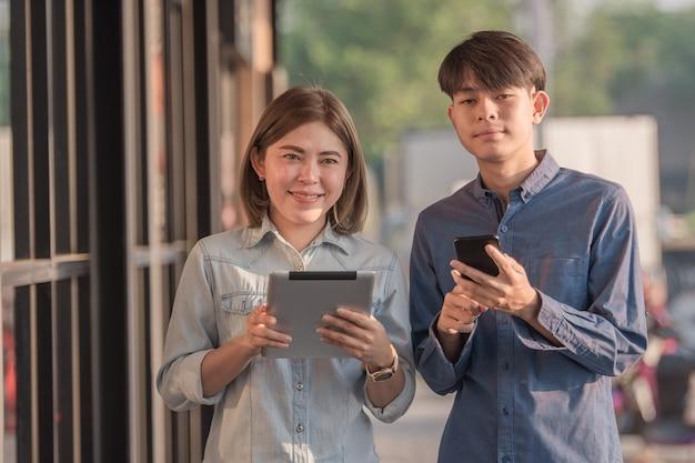 Ludzie używający tabletu i smartfona rozmawiają biznesowo