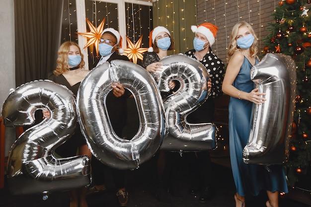 Ludzie w dekoracjach bożonarodzeniowych. koncepcja koronawirusa. grupowe obchody nowego roku. ludzie z balonami 2021.
