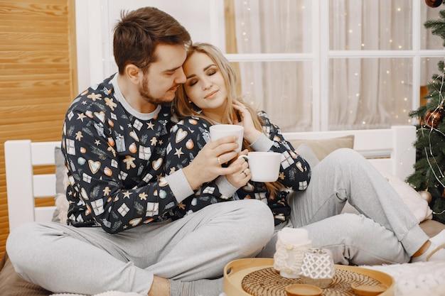Ludzie w dekoracjach bożonarodzeniowych. mężczyzna i kobieta w identycznej piżamie. rodzina na łóżku.