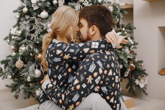 Ludzie w dekoracjach bożonarodzeniowych. mężczyzna i kobieta w identycznej piżamie. rodzina w domu.