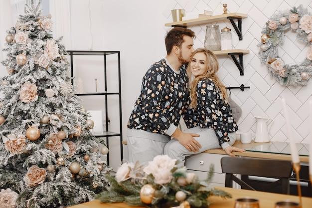 Ludzie w dekoracjach bożonarodzeniowych. mężczyzna i kobieta w identycznej piżamie. rodzina w kuchni.
