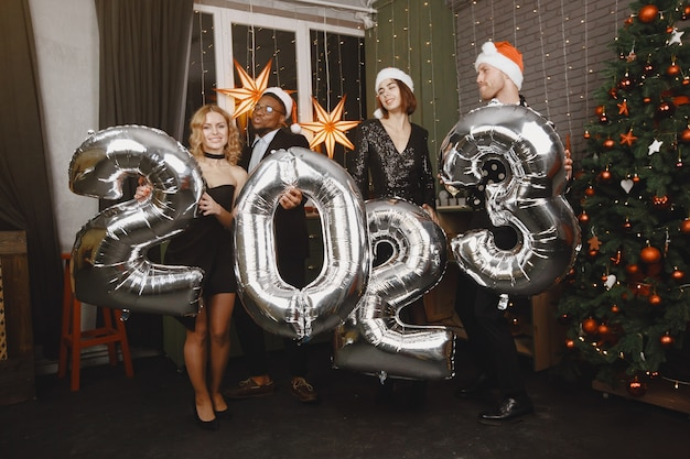 Ludzie w dekoracjach bożonarodzeniowych. mężczyzna w czarnym garniturze. grupowe obchody nowego roku. ludzie z balonami 2023.