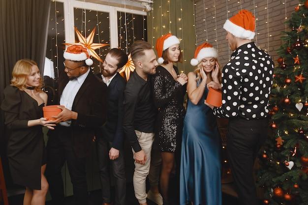 Ludzie w dekoracjach bożonarodzeniowych. mężczyzna w czarnym garniturze. grupowe obchody nowego roku.