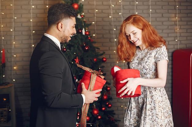 Ludzie w dekoracjach bożonarodzeniowych. mężczyzna w czarnym garniturze. kobieta z czerwonym pudełkiem.