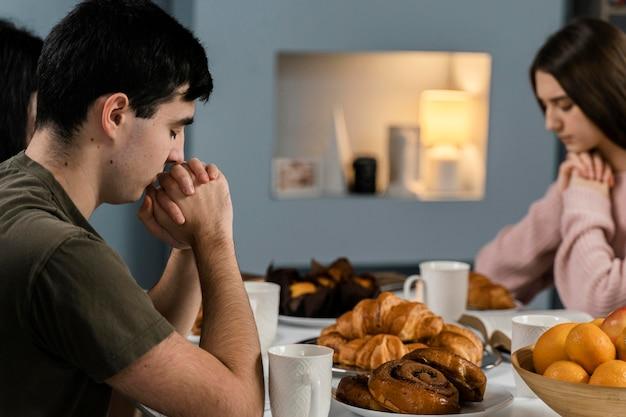 Ludzie w domu modlą się przed obiadem