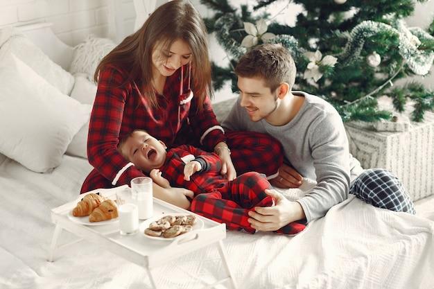 Ludzie w domu. rodzina w piżamie. mleko i rogaliki na tacy.