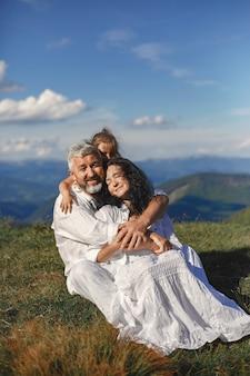 Ludzie w górach. dziadkowie z wnukami. kobieta w białej sukni.