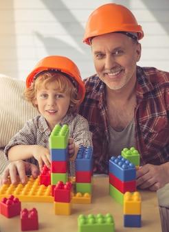 Ludzie w hełmach bawią się budową ustawioną w domu