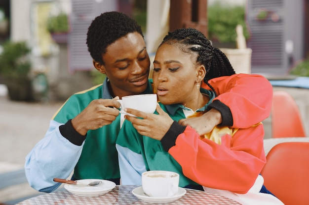 Ludzie w identycznych ubraniach. afrykańska para w mieście jesienią. ludzie przy stole.