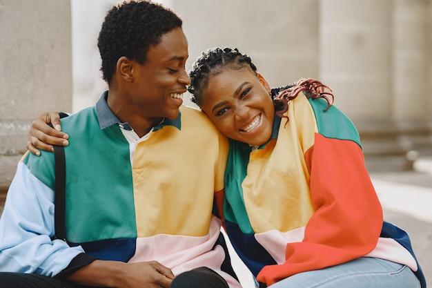 Ludzie w identycznych ubraniach. afrykańska para w mieście jesienią. ludzie siedzący na ulicy.