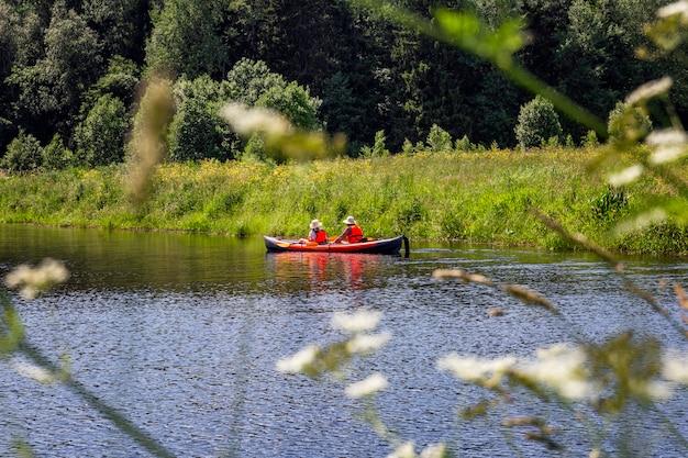 Ludzie w kajaku na rzece na tle lasu. aktywne sporty letnie. piękny krajobraz.