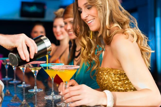 Ludzie w klubie lub barze piją koktajle