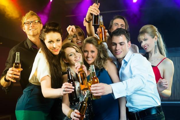 Ludzie w klubie lub barze piją piwo