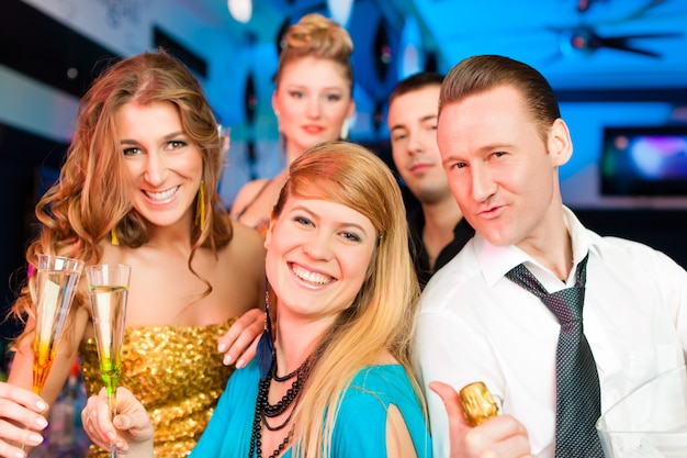 Ludzie w klubie lub barze piją szampana