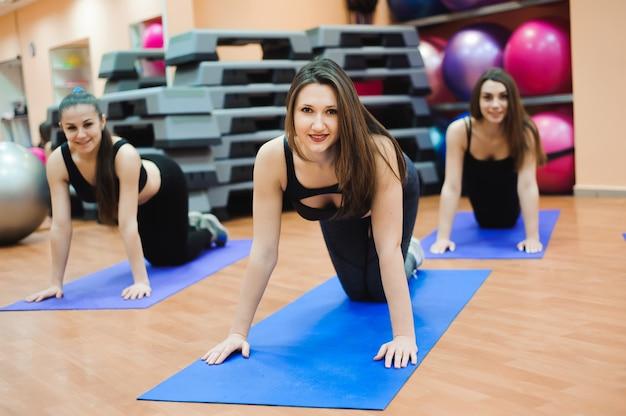 Ludzie w klubie zdrowia z osobistym trenerem, uczący się prawidłowej formy