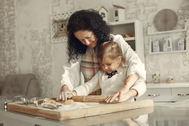 Ludzie w kuchni. babcia z małą córeczką. dorosła kobieta uczy małą dziewczynkę gotować.