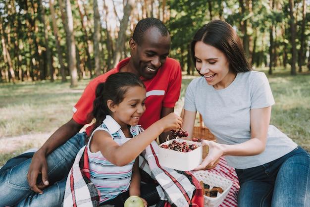 Ludzie w lesie jedzą owoce i odpoczywają.