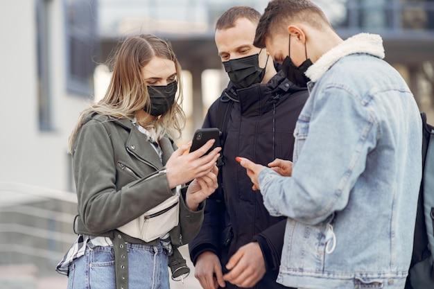 Ludzie w maskach stoją na ulicy